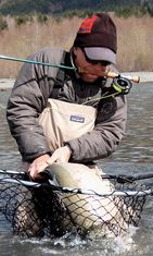 Fly fisherman with a steelhead in a net and pole in his mouth/